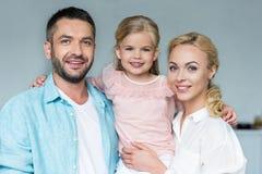 Porträt von glücklichen Eltern mit dem entzückenden wenig Tochterlächeln lizenzfreie stockfotografie