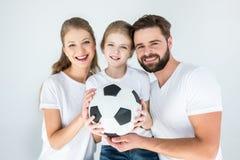 Porträt von glücklichen Eltern und von Tochter, die Fußball hält stockfotos