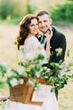 Porträt von glücklichen jungen Jungvermähltenpaaren im Park mit unscharfem Blumendekor am Vordergrund Stockbild