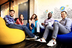 Porträt von glücklichen jungen Leuten in einer Sitzung, die Kamera und das Lächeln betrachtet Junge Designer, die zusammen an a a lizenzfreies stockfoto