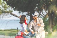 Porträt von glücklichen jungen Liebespaaren auf dem Roller, der in einem Park zur Sommerzeit sich amüsiert Stockfotografie