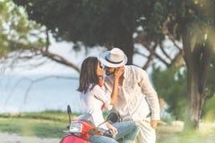 Porträt von glücklichen jungen Liebespaaren auf dem Roller, der in einem Park zur Sommerzeit sich amüsiert Stockfotos