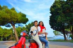 Porträt von glücklichen jungen Liebespaaren auf dem Roller, der sich amüsiert Stockfotografie