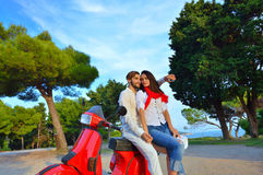 Porträt von glücklichen jungen Liebespaaren auf dem Roller, der sich amüsiert Stockfoto