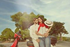 Porträt von glücklichen jungen Liebespaaren auf dem Roller, der sich amüsiert Stockfotos