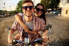 Porträt von glücklichen jungen Paaren auf dem Roller, der Autoreise genießt Stockbild