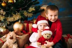 Porträt von glücklichen Kindern mit Weihnachtsgeschenkboxen und -dekorationen Zwei Kinder, die Spaß zu Hause haben Stockbilder