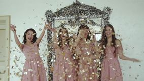 Porträt von glücklichen Mädchen im Abendkleid, das oben zuhause goldene Verpackungen wirft stock video