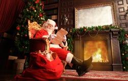 Porträt von glücklicher Santa Claus zu Hause sitzend an seinem Raum nahe Weihnachtsbaum und Weihnachtsbrief oder Wunschliste lese