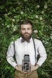 Porträt von hübschen Jungen im Klagenmann mit der Kamera, die im grünen Gras laing und an der Kamera ooking ist Die Mann-Kamera,  Lizenzfreie Stockfotos