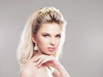 Porträt von herrlichem blondem mit einem schönen Stirnband auf einem grauen b Lizenzfreie Stockfotos