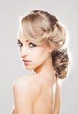 Porträt von herrlichem blondem mit einer schönen Frisur auf einem Grau Stockfotografie