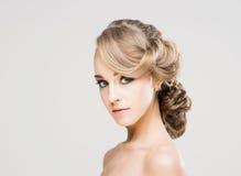 Porträt von herrlichem blondem mit einer schönen Frisur auf einem Grau Lizenzfreie Stockfotografie