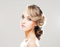 Porträt von herrlichem blondem mit einer schönen Frisur auf einem grauen Hintergrund Lizenzfreies Stockfoto