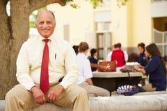 Porträt von Highschoollehrer-Sitting On School-Campus Lizenzfreie Stockbilder