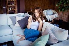 Porträt von ihr sie schön aussehendes attraktives reizendes nettes reizend nettes gewellt-haariges Mädchen, das auf bequemem Sofa lizenzfreie stockfotografie