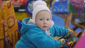 Porträt von 1 5 Jahre alte blauäugige Baby, die Münzenkiddiefahrt spielen Baby dreht Lenkrad eines Spielzeugautos stock video footage