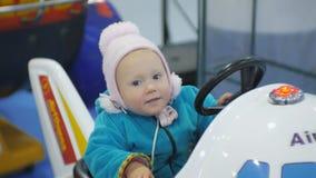 Porträt von 1 5 Jahre alte blauäugige Baby, die Münzenkiddiefahrt spielen Baby dreht Lenkrad eines Spielzeugs stock footage