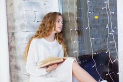 Porträt von 10 Jahren alten Kinderlesebuch auf dem Fenster auf Weihnachten Stockfotografie