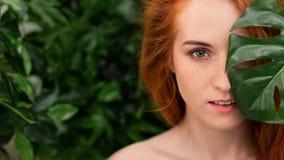 Porträt von jungem und Schönheit in den tropischen Blättern stockfotografie