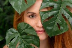 Porträt von jungem und Schönheit in den tropischen Blättern stockbilder