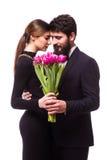 Porträt von jungen Familienpaaren in der Liebe mit Blumenstrauß der lila Tulpenaufstellung kleidete in der klassischen Kleidung a Lizenzfreie Stockbilder
