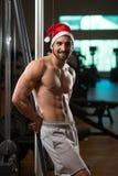 Porträt von jungen Santa Claus Posing And Showing Bodybuilding Lizenzfreie Stockbilder