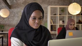 Porträt von jungen schwarzen moslemischen Frauen im hijab, das an Laptop, konzentriert, das Sitzen zwei hübscher Frauen in modern stock video footage