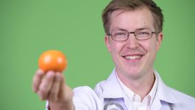 Porträt von junger Mann-Doktor Holding Orange Fruit stock video footage