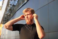 Porträt von junger Sport bemannen Betrieb mit Kopfhörern lizenzfreies stockbild