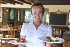 Porträt von Kellnerin-Serving Food In-Restaurant lizenzfreies stockbild