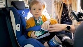 Porträt von lächeln 2 Jahre alte Junge mit dem Spielzeug, das im Kindersitz sitzt Lizenzfreies Stockfoto