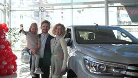 Porträt von lächelnden Familienpaaren mit weniger Tochter auf Händen zeigt Schlüssel zum Fahrzeug, das am Autosalon gekauft wird stock footage