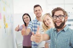 Porträt von lächelnden Geschäftsleuten mit den Daumen oben lizenzfreie stockfotografie