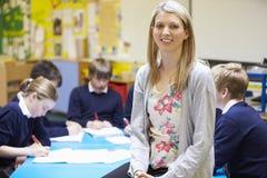 Porträt von Lehrer-In Classroom With-Schülern stockfotos