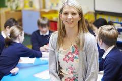 Porträt von Lehrer-In Classroom With-Schülern Stockfotografie