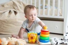Porträt von 10 Monate alten Baby, die mit buntem Spielzeugturm spielen Lizenzfreie Stockfotos
