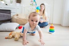 Porträt von netten 10 Monate alten Baby, die auf Boden mit Mutter spielen und Kamera betrachten Lizenzfreie Stockfotografie