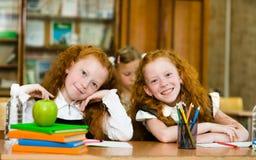 Porträt von reizenden Zwillingsmädchen mit Schulmädchen auf Hintergrund Lo Lizenzfreies Stockfoto