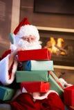 Porträt von Sankt mit Stapel der Weihnachtsgeschenke Lizenzfreies Stockfoto