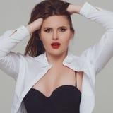 Porträt von schönem plus gelockte junge Frau der Größe Stockfotos