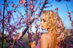 Porträt von schönen Blondinen in blühendem Rosengarten, sonniger Tag der Frühlingsstimmung lizenzfreie stockbilder