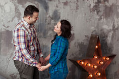 Porträt von schönen jungen Paaren in der zufälligen Kleidung, die, stehend gegen graue Wand umarmt und lächelt Stockbilder