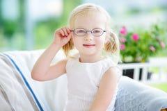 Porträt von schönen tragenden Gläsern des kleinen Mädchens zu Hause stockfotografie