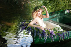 Porträt von Slavic oder von baltischer Frau mit dem Kranz, der im Boot mit Blumen sitzt Sommer Stockfotografie