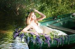 Porträt von Slavic oder von baltischer Frau mit dem Kranz, der im Boot mit Blumen sitzt Sommer Lizenzfreie Stockfotos