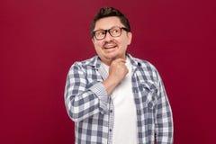 Porträt von smiley hübschen mittleren gealterten Geschäftsmann in der zufälligen karierten Hemd- und Brillenstellung erwägend, di lizenzfreie stockfotografie