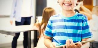 Porträt von smilng Schüler digitale Tablette im Klassenzimmer halten lizenzfreie stockbilder