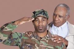Porträt von Soldaten US Marine Corps mit dem Vater, der über braunem Hintergrund begrüßt Stockbild