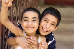 Porträt von 2 spielenden und lachenden Jungen, Straßenhintergrund in Giseh, Ägypten stockbild